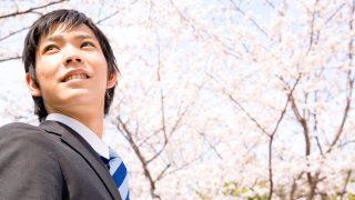 桜の下でほほ笑む新入社員