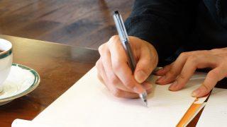 サインする男性の手元
