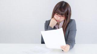 契約書を片手に悩む女性