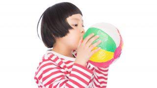 紙風船を膨らませる女の子