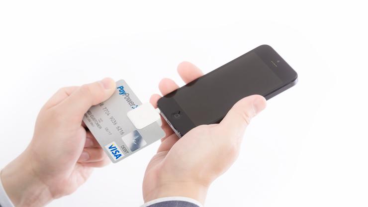 クレジットカードとスマホを持つ男性の手