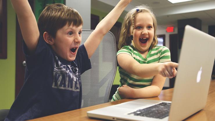 パソコンを見て喜ぶ二人の子ども