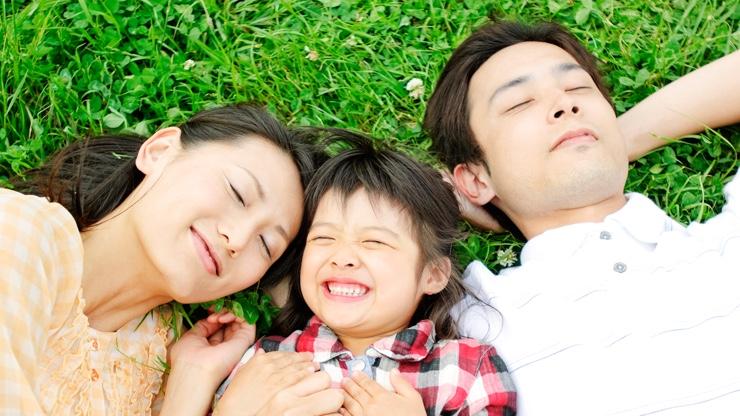 芝生に寝転ぶ三人家族