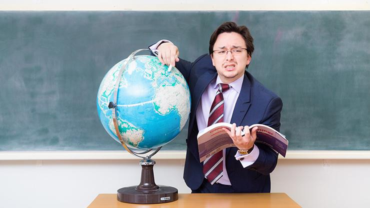 地球儀を指さす教師