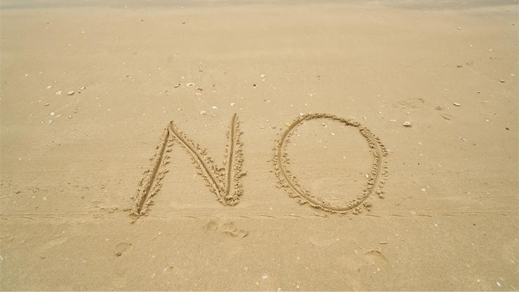砂浜にNOと書かれたイメージ